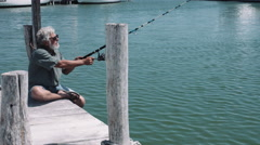Man sitting on pier and fishing Stock Footage