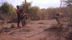 Constructing a barbed wire fence for security, rural Africa, Kenya - stock footage
