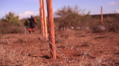 Building a barbed wire fence for security, Africa, Kenya, shallow DOF - stock footage