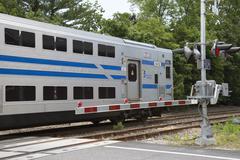 MTA Long Island Railroad train passing a level crossing at Mattituck USA Stock Photos