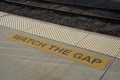 Watch the gap sign at railroad platform edge Stock Photos