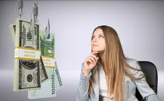 Businesswoman looking at bundle of money - stock photo