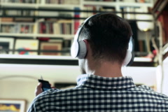 Man sitting at home and listening music on headphones Stock Footage