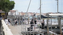 Pier on the waterfront of San Marco in Venice. Passengers awaiting boat - stock footage