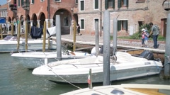 Embankment and pier in Murano island of Venice and parked boats Stock Footage