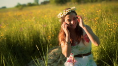 Girl wearing grommet and chatting on cellphone on the meadow Stock Footage