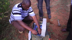 Man setting up wires for geological survey, Kenya, Africa - stock footage