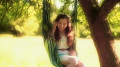 Girl swinging on hammock and chatting on cellphone Stock Footage