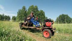 Farmer is riding on the behind tractor along a dirt road Stock Footage