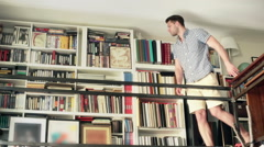 Man walking on the entresol in library and choosing book Stock Footage