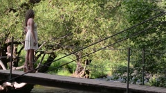 Woman on a bridge above a stream - stock footage