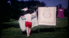 Stock Video Footage of 2309 - mom hangs laundry on clothesline in backyard - vintage film home movie