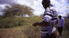 African man writing observations in savannah, Africa - stock footage