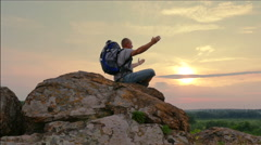 Man  tourist meditating with  raised hands  at sunrise, sunset time. 4K 3840x216 Stock Footage