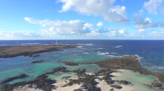 AERIAL: Beautiful coast with big blue lagoons and lighthouse Stock Footage