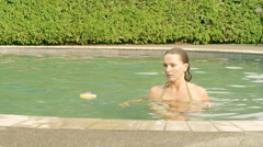 Woman setting toys on the edge of a pool Stock Footage