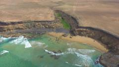 AERIAL: Green oasis in the middle of rocky ocean cliff Stock Footage