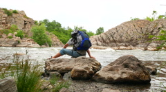 Thoughtful man  tourist with  backpack sit on stone near river. Back view 4K 384 Stock Footage