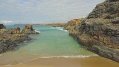 AERIAL: Beautiful exotic beach hidden between the rocky reef Stock Footage
