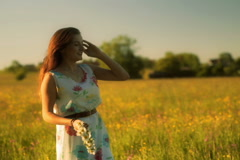 Pretty girl waving hairs and standing on the meadow Stock Footage