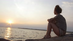 Woman sitting on rocks staring off into body of water Stock Footage