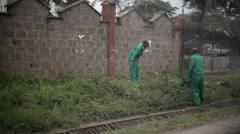 Poor workers cut weeds on roadside, Nairobi, Kenya, Africa Stock Footage