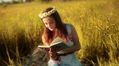 Girl with grommet sitting on the meadow and reading book Stock Footage