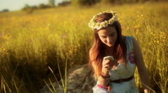 Girl smiling to the camera on the meadow and using smartphone Stock Footage