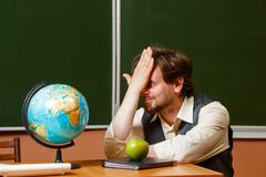 Geography teacher sits in front of a globe. Stock Photos