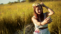 Girl sitting on the meadow with grommet and doing selfie Stock Footage