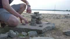 Man finishes building Inukshuks on beach Stock Footage