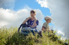 Children resting on a hill in the journey vershign - stock photo