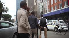 Business men walk in Nairobi city center, tilt to towers, Kenya, Africa Stock Footage
