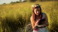 Pretty girl with grommet using tablet and smiling to the camera on the meadow Stock Footage