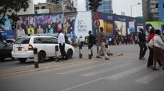 Pedestrians cross big intersection in Nairobi city center, Kenya, Africa Stock Footage