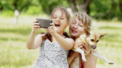 Mother and daughter are  doing selfi  on the smartphone in the park Stock Footage