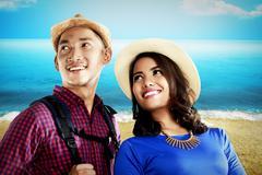 Asian couple travel along on the beach Stock Photos