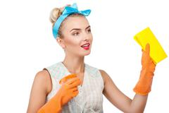Attractive young blond housewife is doing cleanup Stock Photos