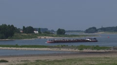 Cargo ship with metal scrap downstream in a bend of the River Waal Stock Footage