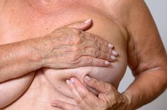 Elderly lady doing a breast examination - stock photo