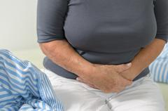 Woman with stomach ache clutching her stomach Stock Photos