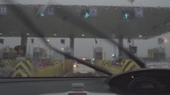 Rain splatters car windshield during storm while passing the toll to highway Stock Footage