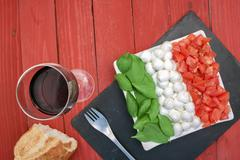 a horizontal view of a caprese salad with a glass of wine - stock photo