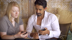 A young couple share technology together as they surf on their mobile devices Stock Footage