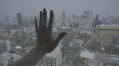 Hand touching glass of window with the cityscape view outside - stock footage
