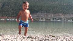 Smiling toddler comes from the sea Stock Footage