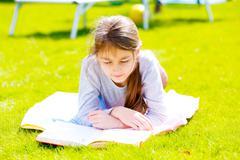 Children girl read book on green grass Stock Photos