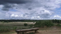 Dark clouds above a vacant bench in Veluwe National Park THE NETHERLANDS Stock Footage