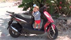 Toddler in red nappies stands on red scooter bike- Stock Footage