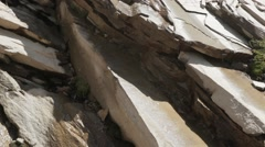 Mountain flat rocks with water dripping from melting snow above - stock footage
